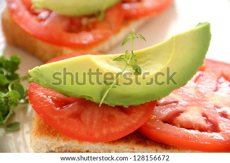 Delicious fresh slice of avocado with tomato and thyme on toast. - stock photo
