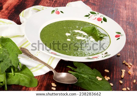 Delicious fresh spinach soup with fresh spinach leaves and bread on wooden background, top view. Culinary soup eating.  - stock photo
