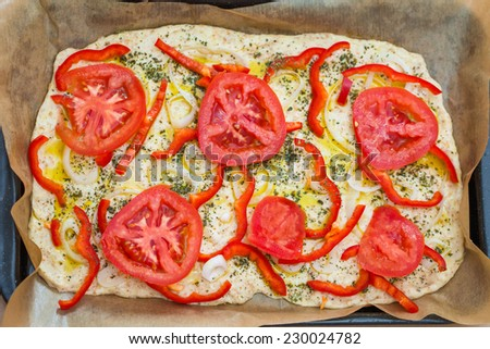Delicious fresh traditional Italian focaccia bread with tomatoes, red peppers, onions, basil and olive oil on pan ready to cook - stock photo