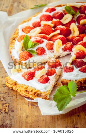 Delicious freshly baked strawberry tart with whipped cream and sliced banana garnish on a crisp golden pastry pie crust with a single slice removed - stock photo