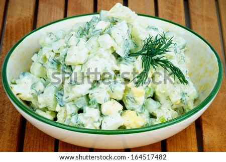 Delicious Freshly Made Creamy Potato Salad Garnished with Dill in Beige Bowl closeup on Wooden Plank background