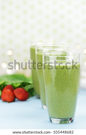 Delicious freshly made Spinach and Strawberry smoothies made with cold milk, yogurt, spinach and strawberries. Extreme shallow depth of field with selective focus on glass in foreground. - stock photo