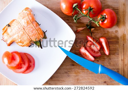 Delicious freshly roasted fresh salmon fillet served with fresh sliced vine tomatoes being prepared in a kitchen with a modern blue kitchen knife, close up view from above on a wooden counter - stock photo