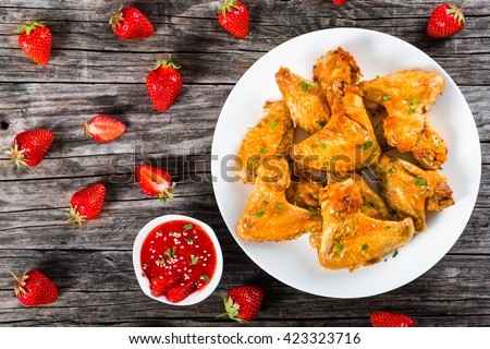 delicious fried chicken wings on a white dish with strawberry sauce on a gravy boat and strawberries on a wooden table, top view  - stock photo
