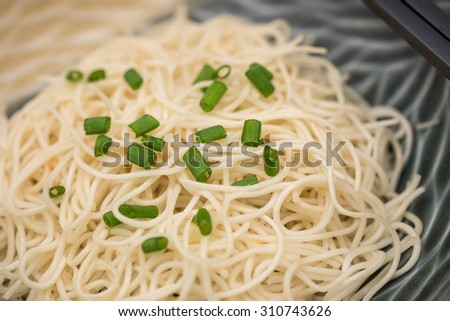 Delicious fried Chinese noodles with chopsticks on bamboo plate mate for local Thai food background - stock photo