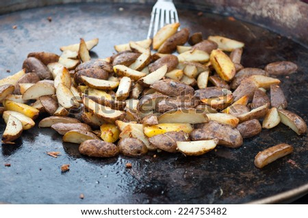 Delicious fried potatoes on the fire in a large pan. - stock photo