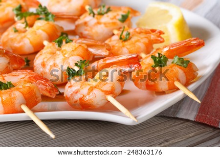 Delicious fried shrimp on wooden skewers close-up on a plate. horizontal  - stock photo