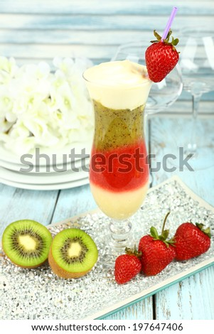 Delicious fruit smoothie on wooden table, close up