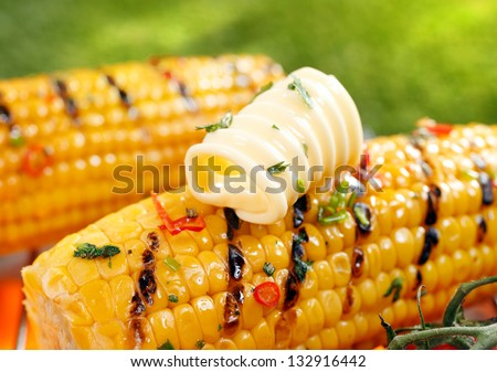 Delicious golden grilled corn on the cob served outdoors with a curl of fresh farm butter - stock photo