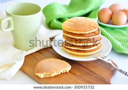 Delicious golden pancakes cooked on dry pan and served for breakfast with honey and kiwi fruit on a wooden board, one pancake half eaten. Still life, copy space - stock photo