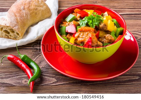 Delicious goulash on wooden table