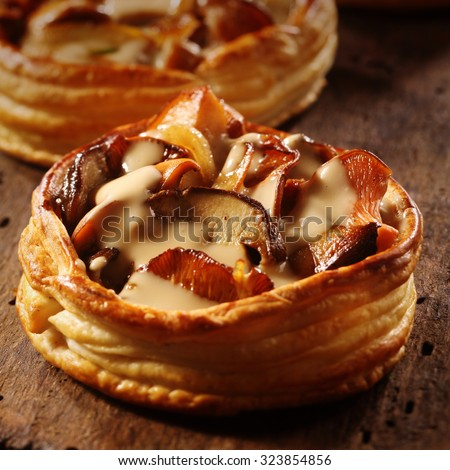 Delicious gourmet individual mushroom pie in a flaky pastry base with assorted fresh seasonal autumn fungi in a creamy savory sauce - stock photo