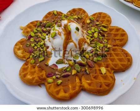 Delicious greek waffle with caramel, pistachio nuts and ice cream