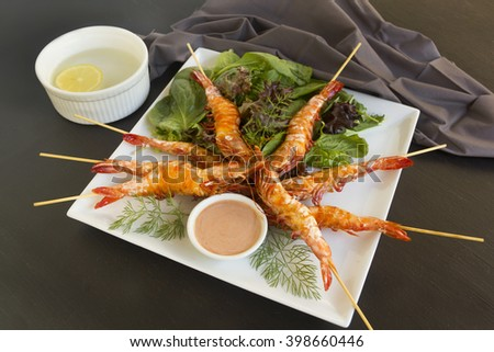 Delicious grilled barbequed shrimps on skewers with a dipping sauce and fresh garden salad.