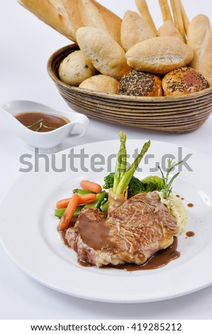Delicious grilled beef steak served with sauce and cooked vegetables on white plate - stock photo