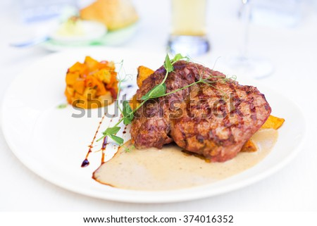Delicious grilled beef steak with colorful vegetable garnish on a white plate - stock photo