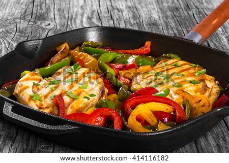 Delicious Grilled Chicken breast fillet and fried bell pepper on a skillet on an old rustic table, horizontal top view - stock photo