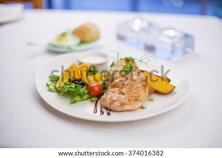 Delicious grilled chicken breasts with potatoes and colorful garnish  - stock photo
