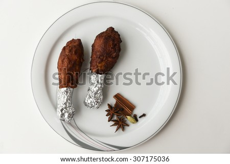 Delicious Grilled chicken legs and spices ( star anise, cinnamon sticks and clove ) served on a white plate on a white background. Tasty Roasted chicken drumstick wrapped in aluminum foil and spices - stock photo