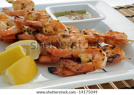 Delicious grilled shrimp with lemon and dipping sauce. - stock photo