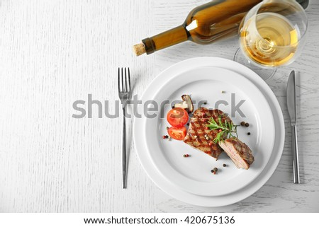 Delicious grilled steak on plate with white wine - stock photo