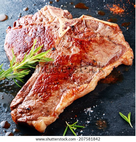 Delicious grilled t-bone steak on a hot griddle seasoned with fresh rosemary, herbs and spices in a steakhouse or restaurant - stock photo