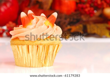 Delicious Halloween cupcake with butter cream frosting and fall foliage in the background