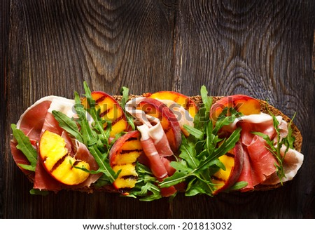 Delicious ham sandwich with grilled peaches and arugula on an wooden background with place for text. - stock photo