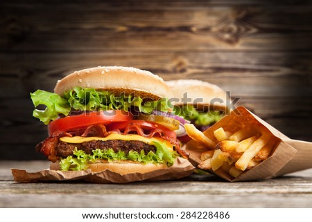 Delicious hamburger and fries on wooden background - stock photo