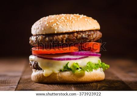 Delicious hamburger on dark wooden background - stock photo