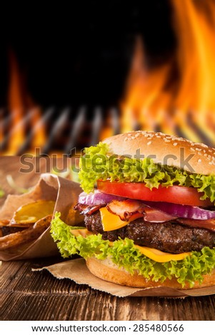 Delicious hamburger on wood with fire on background - stock photo