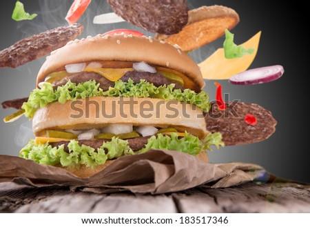 Delicious hamburger on wooden background - stock photo