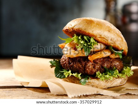Delicious hamburger with beef and grilled fresh shrimp garnished with lettuce served on pieces of brown paper on a rustic wooden counter, close up side view with copyspace - stock photo