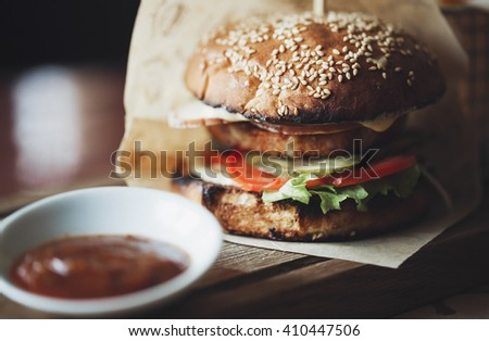 Delicious hamburger with beef, tomato, cucumber and fresh salad fried on a grill and put between two bagels with sesame seeds. Unhealthy but so tasty fast food. Close up photo in macro mode - stock photo