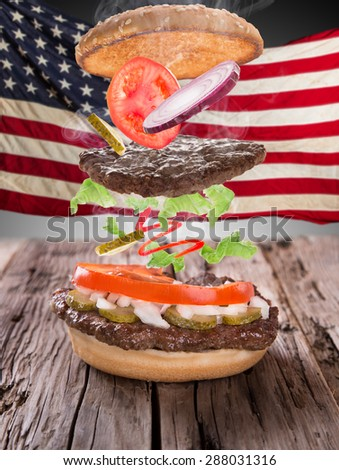 Delicious hamburger with fire flames and american flag on wooden background - stock photo