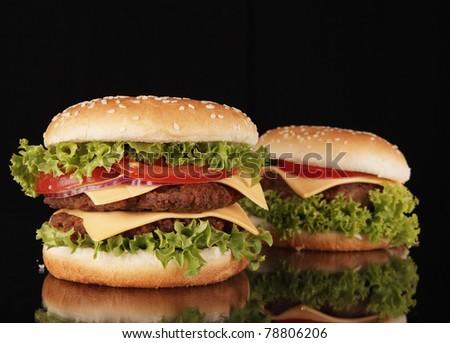 Delicious hamburgers isolated on black background - stock photo
