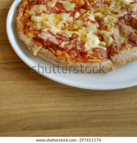 delicious hawaiian rustic style pizza made with fresh pineapples,ham and mozzarella cheese - stock photo
