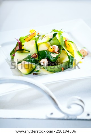 Delicious healthy fresh summer salad served outdoors on a white table in sunlight with the scrolled white metal arm of garden furniture in the foreground - stock photo