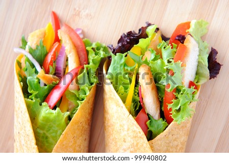 Delicious healthy meal consisting of a chicken burrito with plenty of fresh raw salad - stock photo
