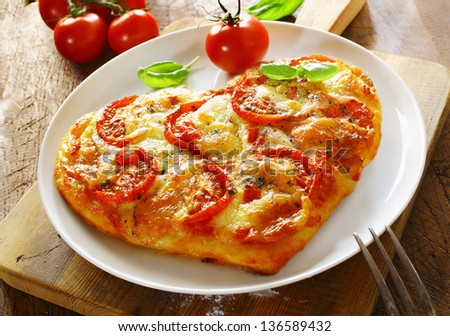 Delicious heart shaped Italian pizza with a topping of tomato and melted cheese served on a plain white plate with a fresh tomato and basil - stock photo