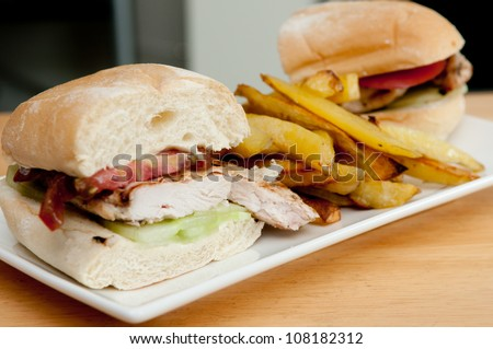delicious heirloom tomatoes and chicken with mayo, irish cheddar cheese and hand cut home fries, plus sliced cucumber on a portuguese roll - stock photo