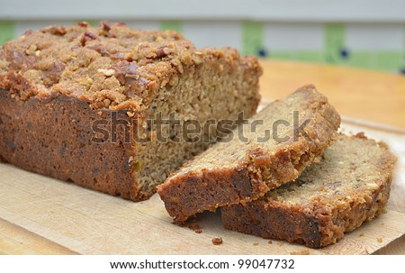 Delicious, Home baked Banana Bread, Sliced on a Cutting Board on a Wooden Kitchen Table - stock photo