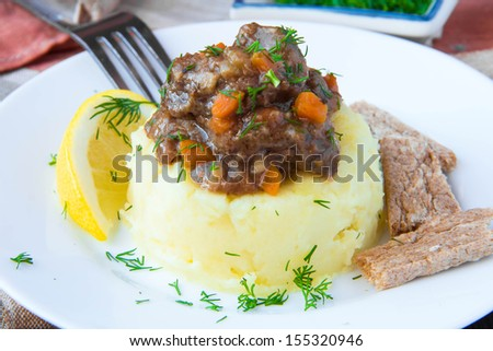 Delicious home-cooked dinner, mashed potato with stew of beef meat and gravy, flavorful dish - stock photo