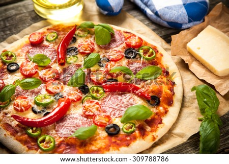 Delicious home made pizza on wooden background - stock photo