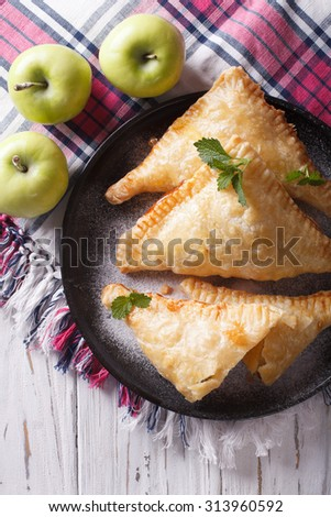 Delicious homemade apple pie turnover close-up on a plate. vertical top view - stock photo