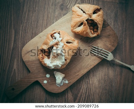 Delicious homemade apple strudel with ice cream on wooden background. Toned picture - stock photo