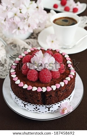 Delicious homemade chocolate cake with raspberry-flower garnish.Selective focus. - stock photo