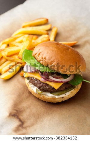 Delicious homemade hamburger with french fries on paper background - stock photo
