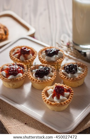 Delicious homemade mini berry tarts and custard on wooden cutting board - stock photo