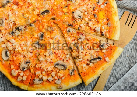 Delicious homemade pizza with cheese and mushrooms on a wooden table with a creative decoration tomato cheese eggs and other ingredients. soft focus - stock photo